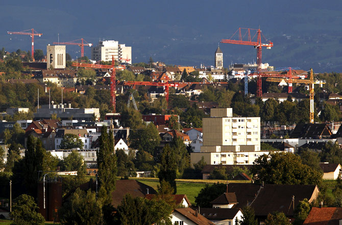Apartment buildings and construction cranes are pictured in Affoltern, outside Zurich.