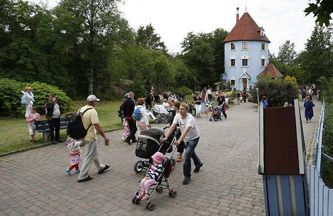 Visitors walk down the main street at Moomin World theme park in Naatali, Finland.