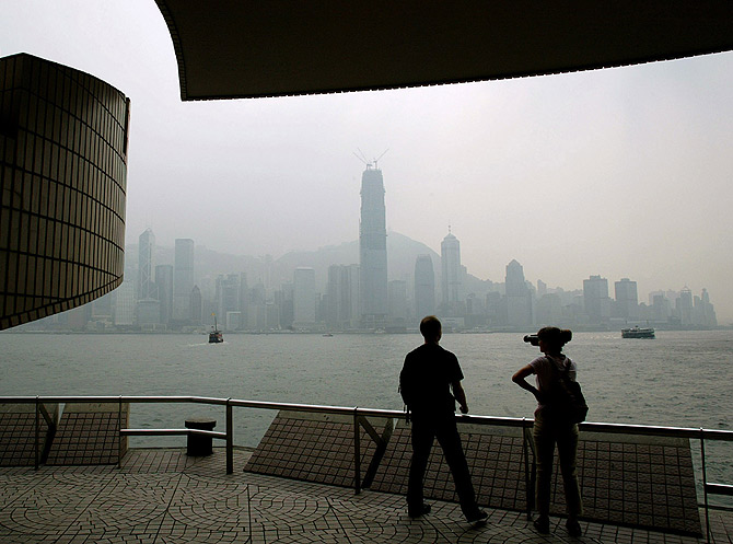 Tourists look out over Victoria harbor and the central business district.