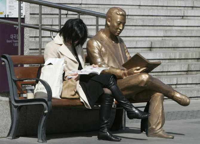 A woman reads a book beside a bronze statue in front of Sejong Centre
