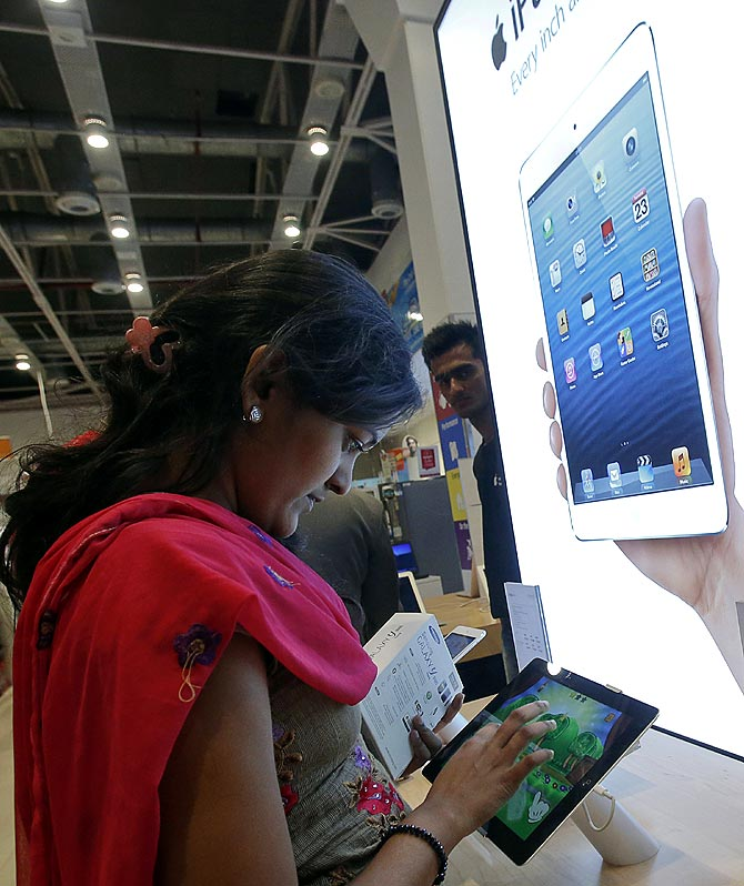 A customer tries out an Apple iPad Mini in the Apple specialty section of a Croma retail store