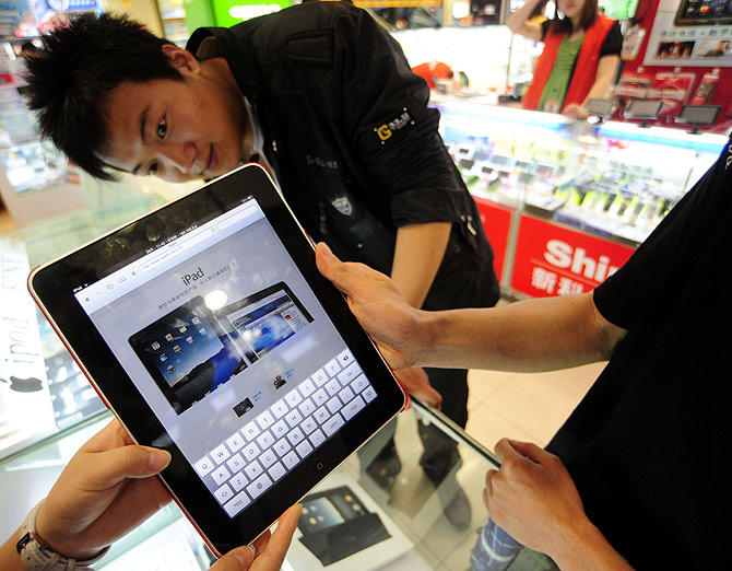 A shop assistant (L) displays an iPad at an electronic products store