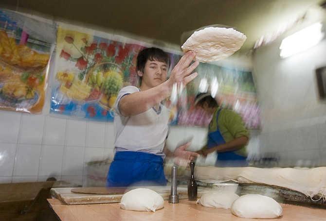 Men bake traditional bread at a private bakery in Tashkent, Uzbekistan.