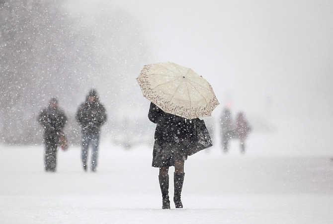 People walk during heavy snowfall in central Minsk, Belarus.