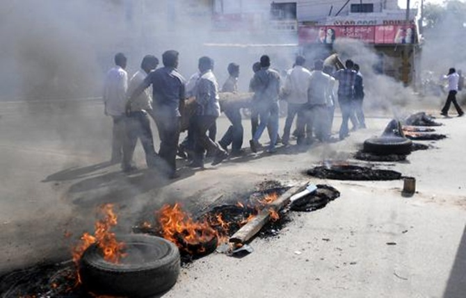 Protesters carry a wooden log past burning tyres during a protest against the creation of Telangana state, in Ananthapuram district in Andhra Pradesh.
