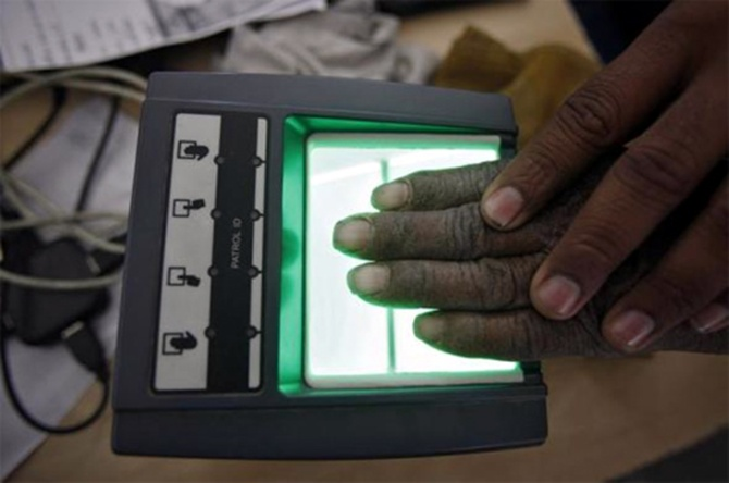 A villager goes through the process of a fingerprint scanner for the Unique Identification (UID) database system at an enrolment centre at Merta district in Rajasthan.