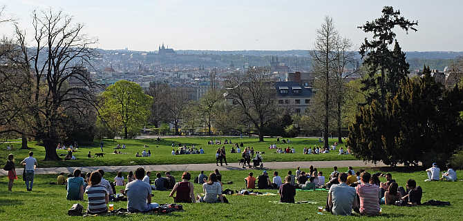 People relax in a park during a warm spring day in Prague, Czech Republic.