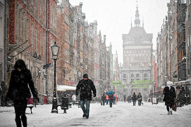 People walk on the main street in the Old Town during heavy snowfall in Gdansk, northern Poland.