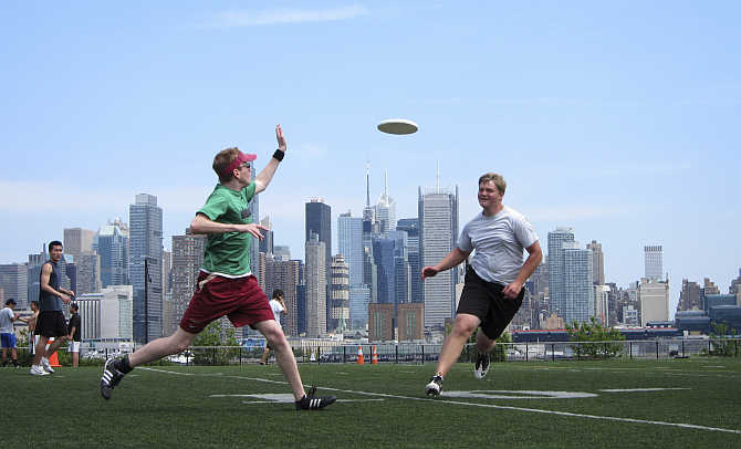 With the skyline of New York behind them, people play a game of ultimate frisbee in a park in Weehawken, New Jersey, United States.