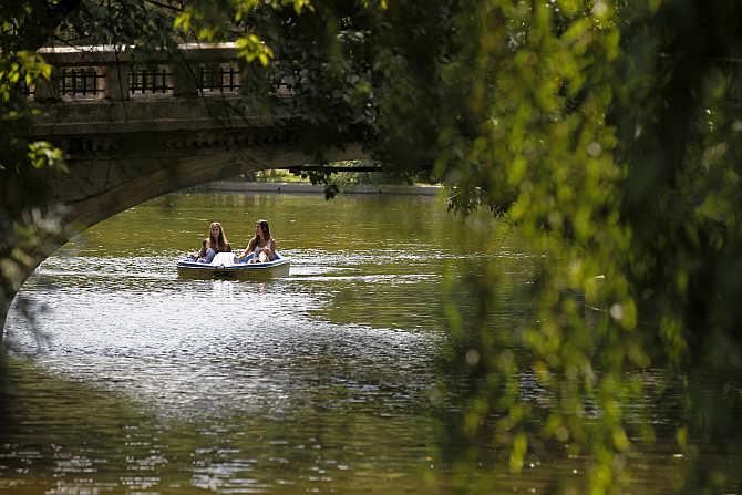 Two girls ride a water bicycle in a park in Bucharest as temperature reached 36 degrees Celsius in southern Romania.