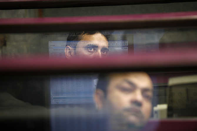 Brokers monitor the market from their booth during a trading session at the Karachi Stock Exchange, Pakistan.