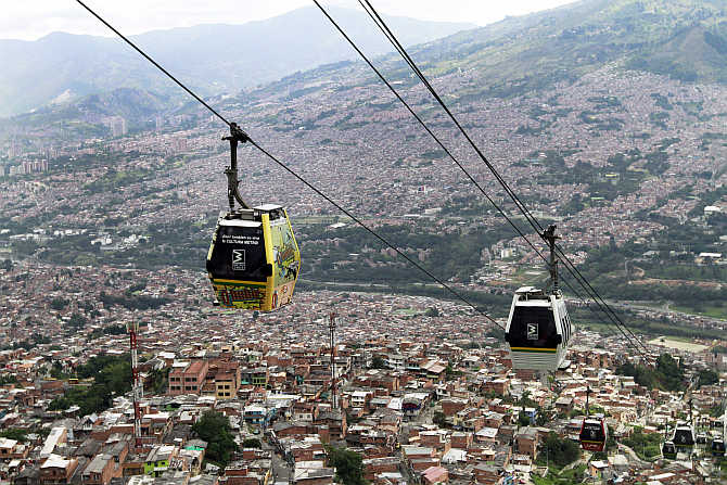 Cable cars pass above the town of Medellin, Colombia.