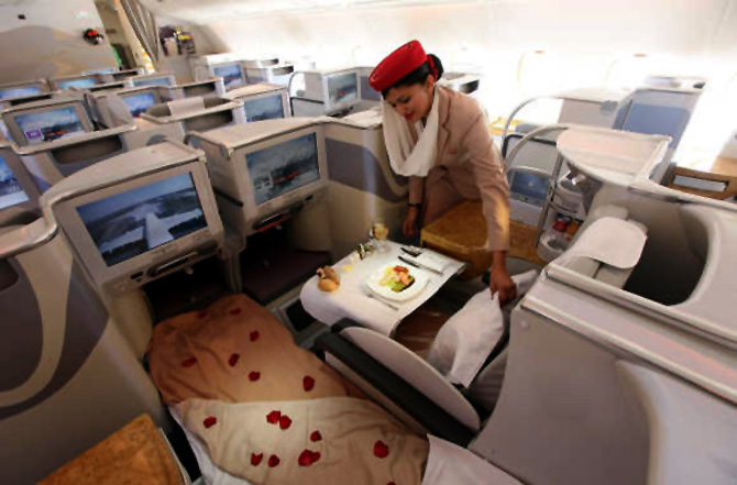 A stewardess adjusts a pillow in the business-class section of an Emirates Airbus A380.