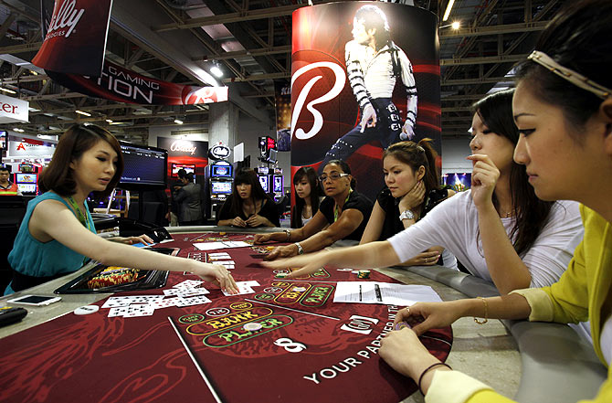 Attendants working for U.S. slot machine maker Bally Technologies learn a poker game before introducing it to visitors at Gaming Expo Asia in Macau.