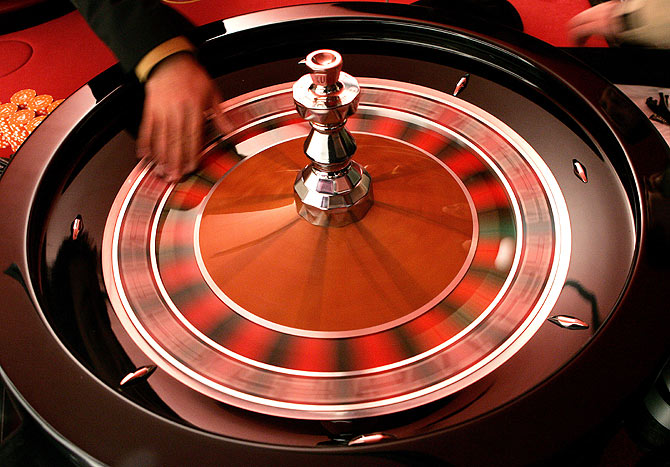 A croupier turns the roulette in a casino.