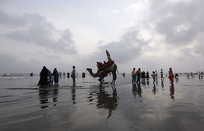 A man talks to customers while offering them a camel ride along Karachi's Clifton Beach, Pakistan.