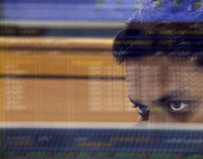 A stock broker looks at a terminal while trading at a stock brokerage firm in Mumbai.