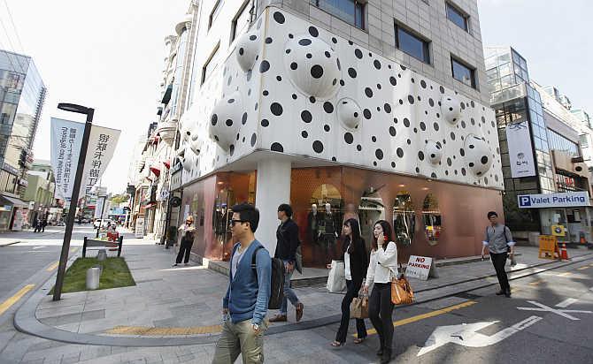 People walk along Apgujeong Rodeo Street in the Gangnam area of Seoul, South Korea.