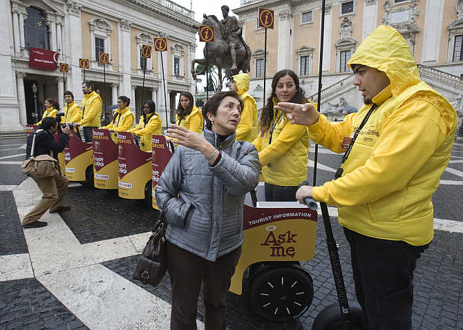 A tourist asks for directions from one of several mobile guides on Segway 'chariots' at city hall in Rome, Italy.
