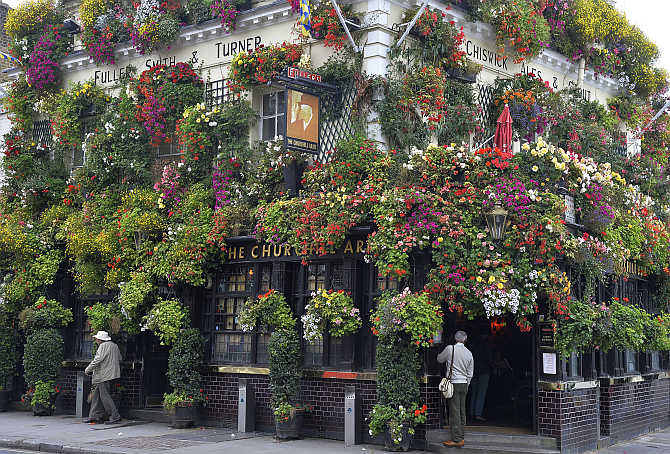 A customer stands outside The Churchill Arms pub in central London. The 18th century public house has twice won the 'London in Bloom' competition for its floral displays and hanging baskets which adorn the outside.