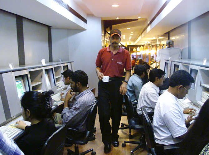 A waiter serves coffee to students surfing the Internet at a cafe in Bangalore.