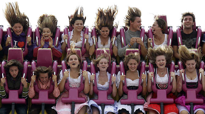 People enjoy a ride in a roller coaster at the traditional Bavarian beer festival Oktoberfest in Munich, Germany.