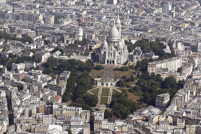 An aerial view shows the Sacre Coeur Basilica and rooftops of residential buildings on Montmartre in Paris, France.