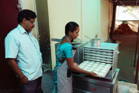 Idlis being prepared at one of the breakfast centres.