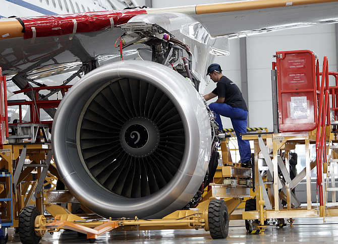 An employee installs an engine for an A320 plane at the final assembly line of Airbus factory in Tianjin municipality, China.