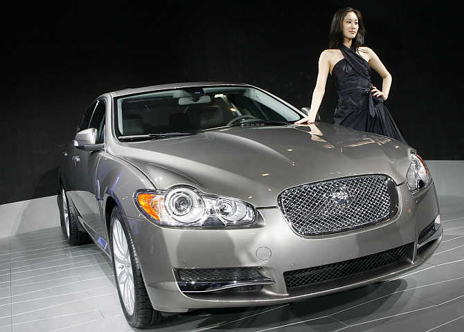 A model poses beside the Jaguar XF in Beijing, China.