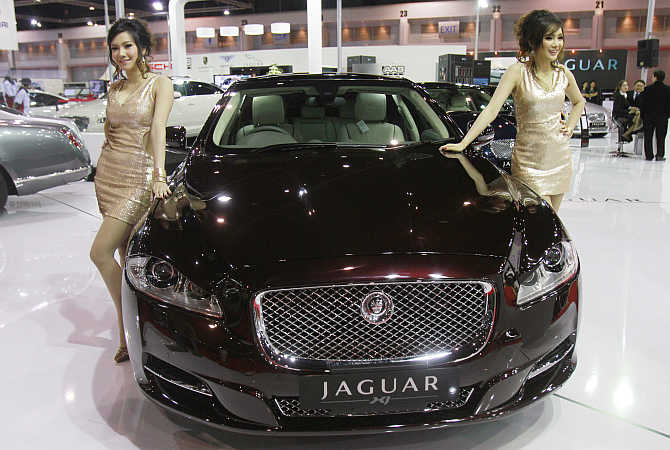 Models pose beside a Jaguar XJ.