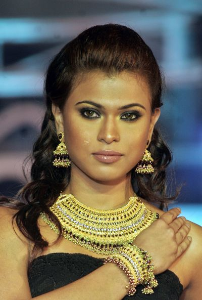 An Indian model wears gold jewellery in a fashion show.