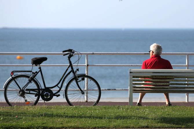 An elderly man sits on a bench next to his bicycle to take in the sun.
