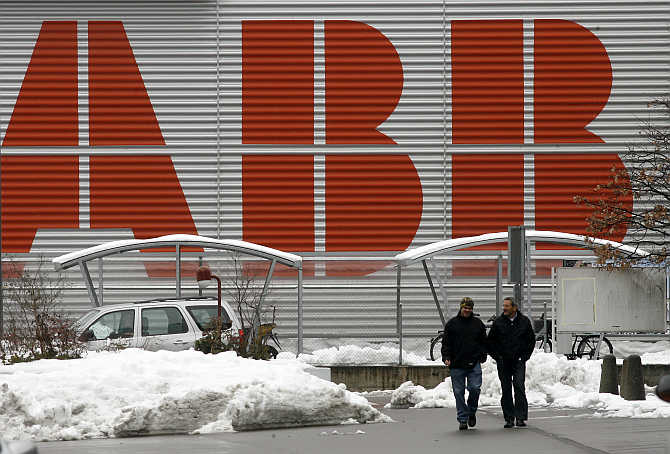 Two men walk in front of the logo of Swiss engineering group ABB in the town of Baden west of Zurich. ABB is another competitor of Havells.