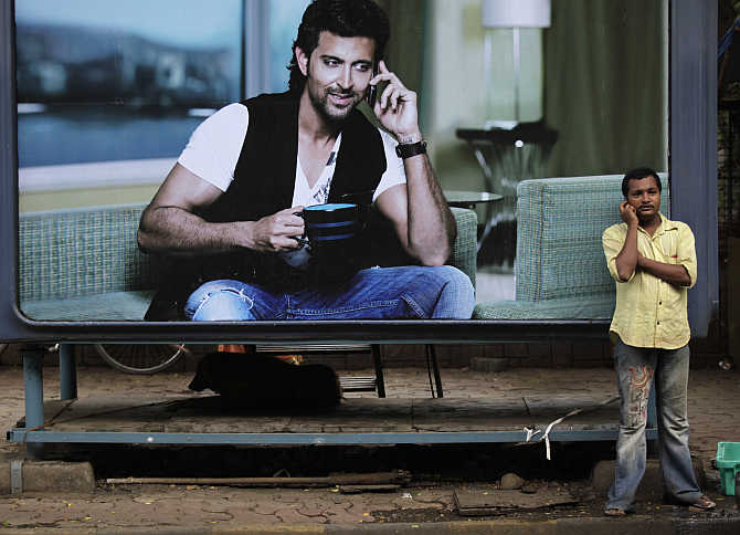 A man makes a phone call in front of a billboard in Mumbai.