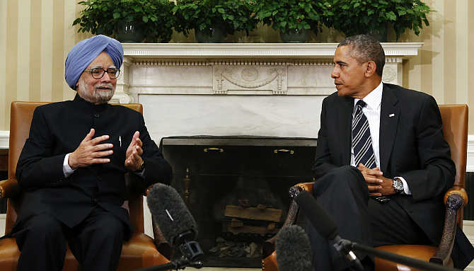 Indian Prime Minister Manmohan Singh speaks as US President Barack Obama looks on, during their meeting in the Oval