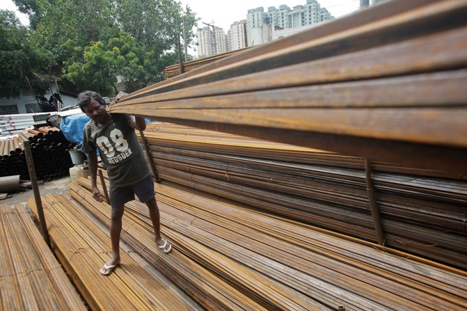 A worker loads iron rods in a truck at an iron and steel market in an industrial area in Mumbai.