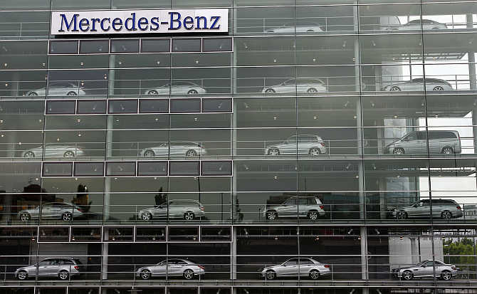 Mercedes-Benz cars are displayed in the windows of a dealership of German car manufacturer Daimler in Munich, Germany.