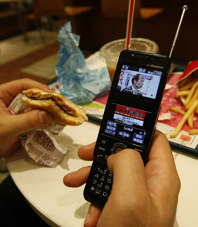 A man watches television through his mobile phone at a fast food restaurant in Tokyo, Japan.