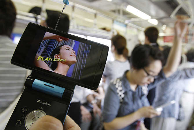 A man watches television on his mobile phone while commuting on a train in Tokyo, Japan.