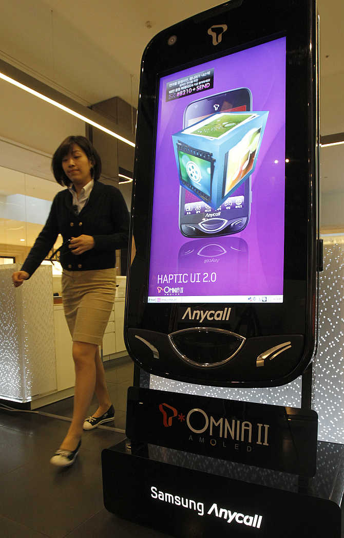 An employee of Samsung Electronics walks past a large-scale replica of one of its mobile phones displayed for visitors at the company's headquarters in Seoul, South Korea.