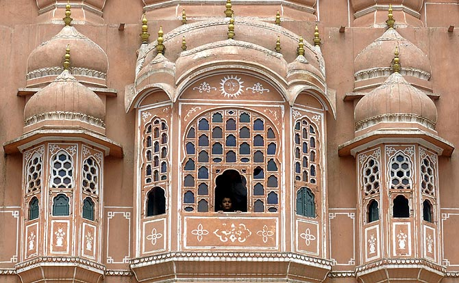 A boy looks out from a window of Hawa Mahal also known as Palace of Winds in Jaipur.