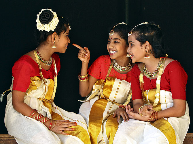 School girls wearing traditional costume share a laugh backstage as they wait to perform during festivities marking the start of the annual harvest festival of Onam in the southern Indian city of Chennai.