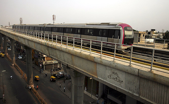 A Namma Metro (Kannada for Our Metro) train travels along an elevated track as traffic passes below in the Indira Nagar area of Bangalore.