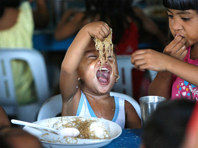 A boy enjoys free meals during a feeding program at a slum community.
