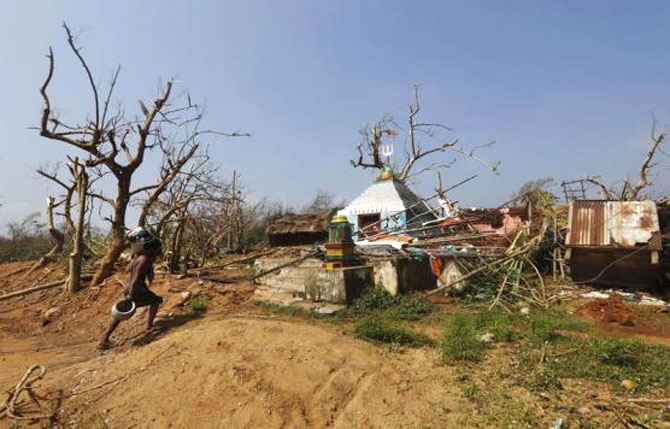 A man carries his belongings as he walks past a damaged temple after Cyclone Phailin hit Arjyapalli village, in Ganjam district in Odisha.
