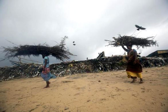 Fisherwomen carrying wood walk past an eroded shore after Cyclone Phailin hit Puri.