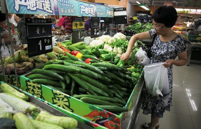 A customer selects green peppers at a supermarket in Beijing.