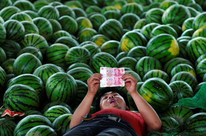 A watermelon vendor looks at yuan banknotes at a market in Changzhi, Shanxi province.