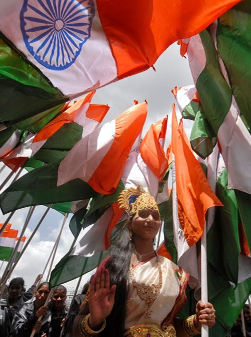 A woman dressed as Mother India poses with India's national flags during the country's Independence Day celebrations in Hyderabad.